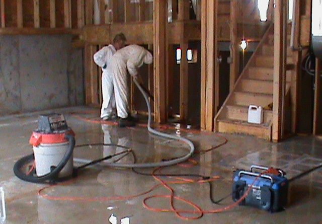 Two men cleaning concrete floor prior to renovations
