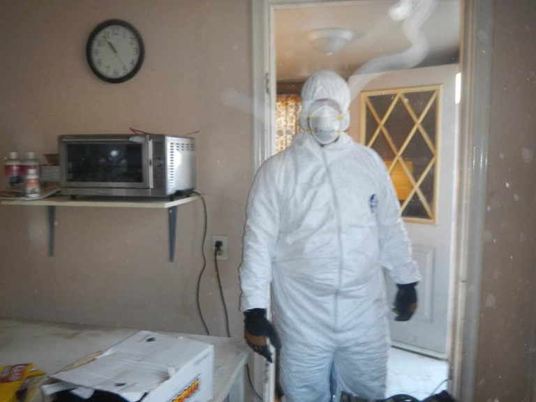 Suited up extreme cleaner preparing to clean hoarder house