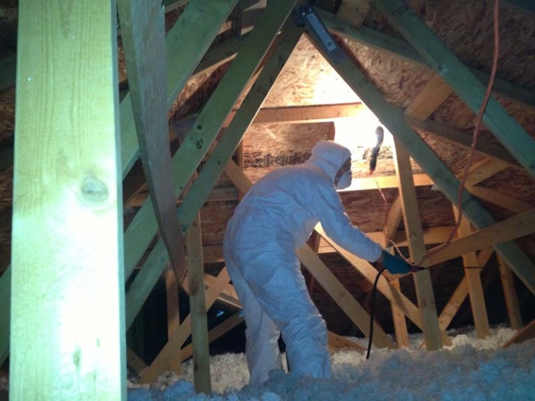 Worker in attic wearing personal protection suit