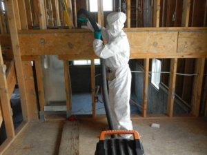 Technician In Personal Protection Suit Cleaning Home Under ConstructionWith Vacuum