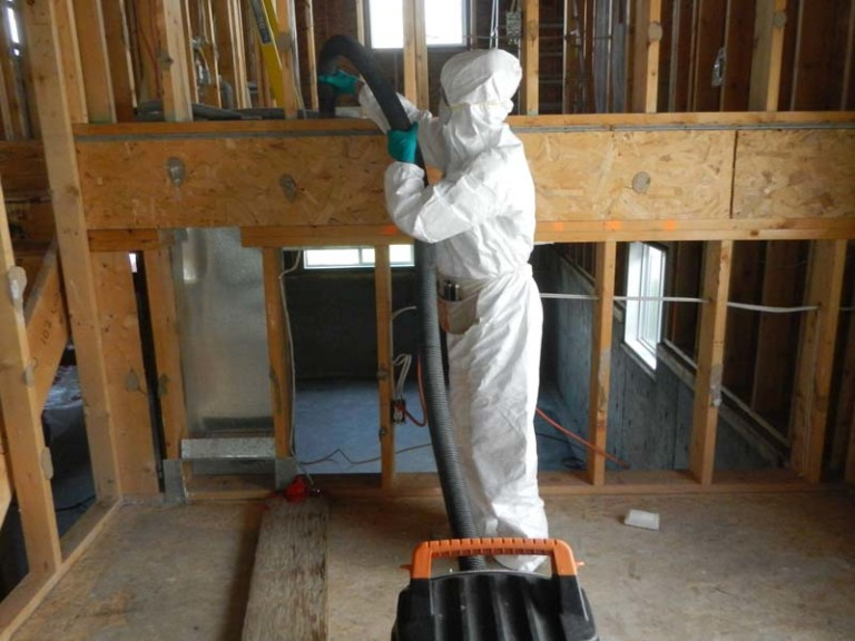 Technician in PPE vacuuming home under construction