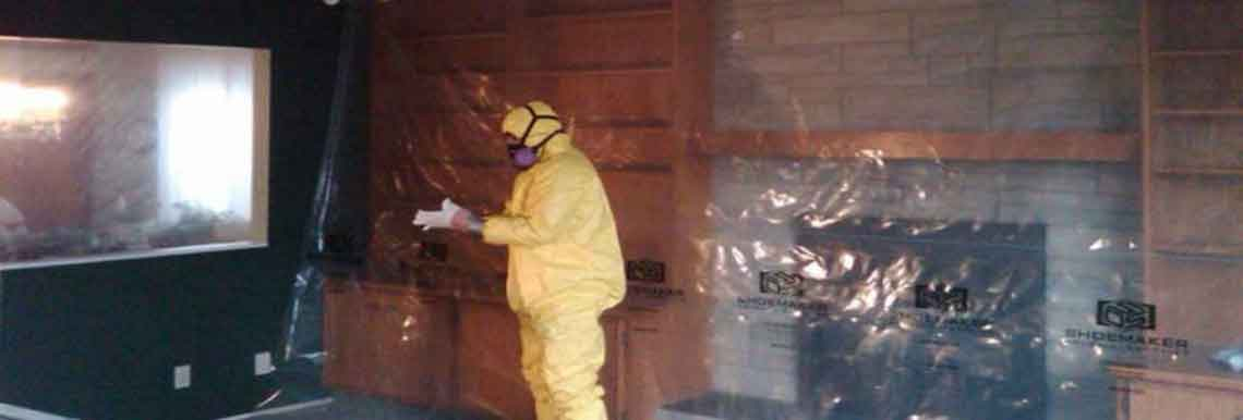 Hazmat technician in yellow suit removing asbestos