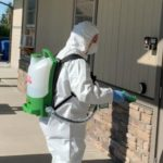 Hazmat technician in white coveralls suit spraying disinfectant on door