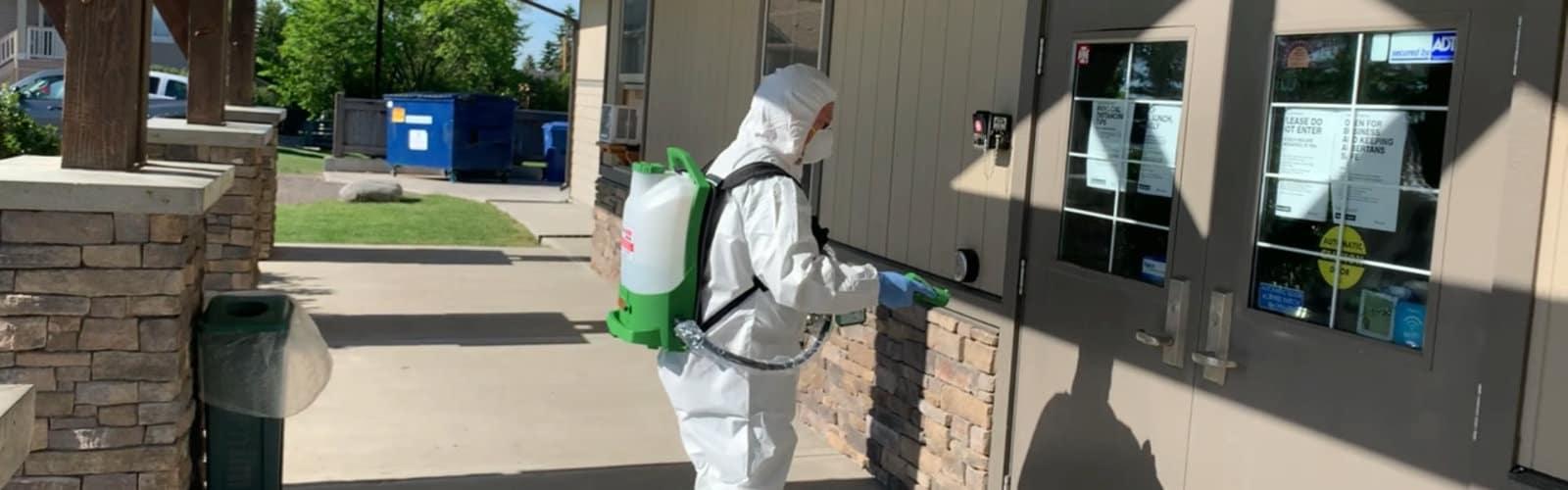 Hazmat technician in white coveralls suit spraying disinfectant on door