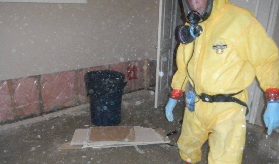 Hazmat technician in PPE cleaning dust filled room