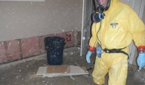 Hazmat technician in PPE cleaning dust filled room