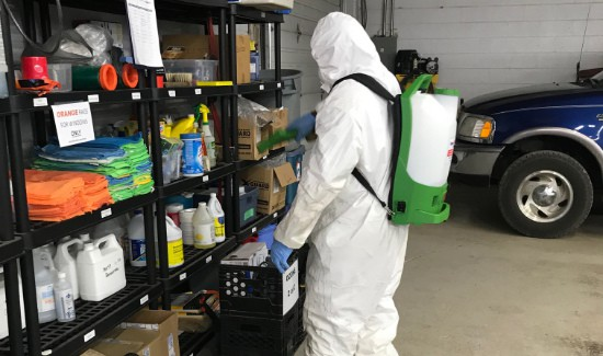 Hazmat technician in PPE disinfecting inventory on shelving