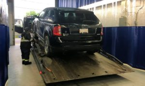 Towed recovered stolen car unloaded at shop